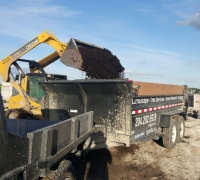 skid steer loading a dump trailer with soil