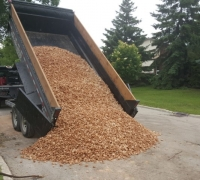 dump trailer dumping load of red shael aggregate