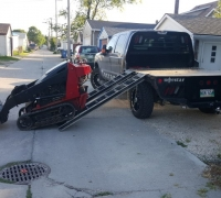 unloading mini skid steer from flatdeck truck